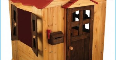 Children's wooden house with their hands